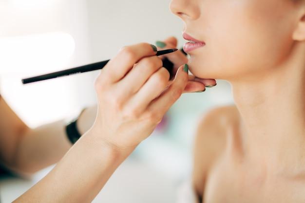 메이크업 아티스트는 여자의 얼굴 클로즈업에 얇은 브러시로 립스틱을 바릅니다.