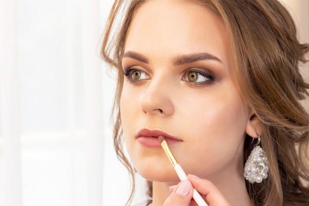 메이크업 아티스트는 모델에 메이크업을 적용합니다. 립스틱 용 립 페인트 브러시. 아름다운 소녀 모델, 초상화. 메이크업의 누드 색상. 결혼식, 저녁 화장.