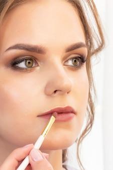 メイクアップアーティストがモデルにメイクを適用します。口紅用リップペイントブラシ。美しい少女モデル、肖像画。メイクのヌードカラー。結婚式、イブニングメイク。