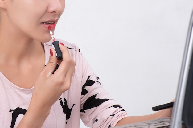 メイクアップアーティストは赤い口紅を塗ります。若い美容アジアモデルの女の子の唇を描く。白い背景で隔離のプロセスでメイクアップ