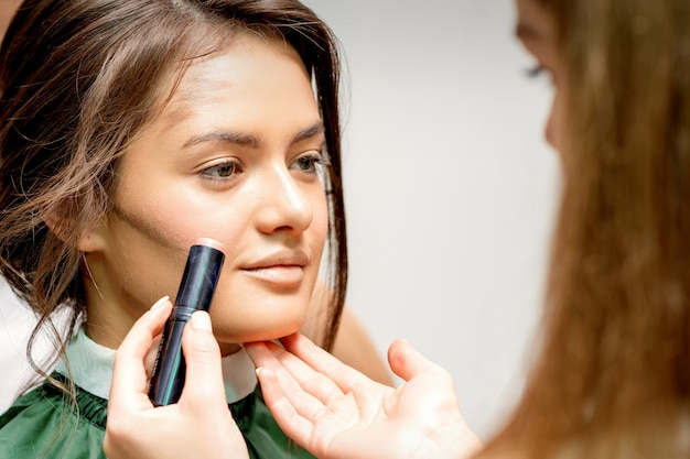Makeup artist applying cream blush stick foundation on cheek of young caucasian woman