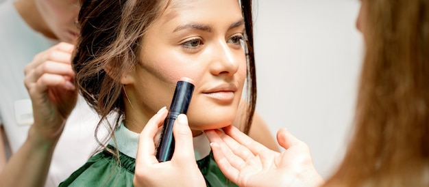 Makeup artist applying cream blush stick foundation on cheek