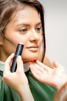 Визажист наносит крем-румяна на щеку молодой кавказской женщины
