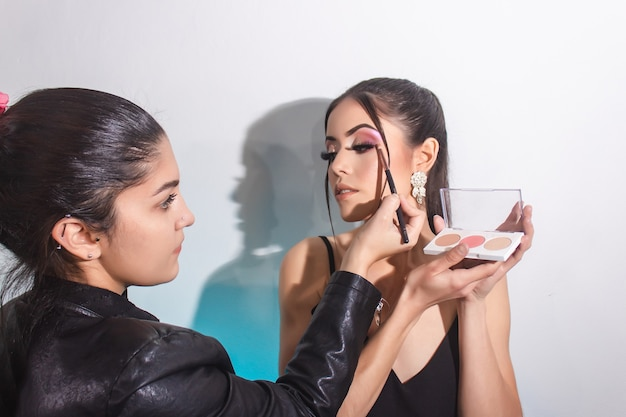 Makeup artist applying eye contour. beautiful girl with makeup on white background.