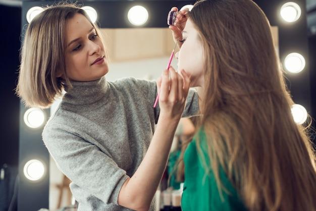 Makeup artist applying eyeliner on model