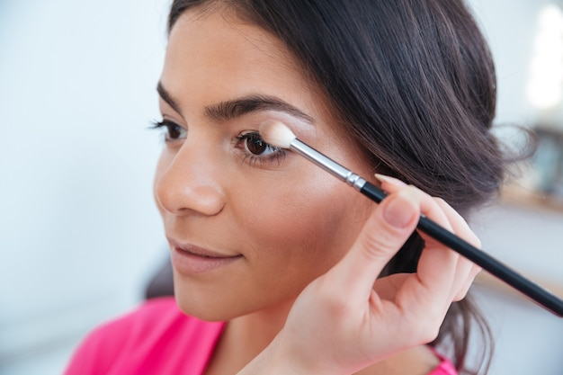 Makeup artist applying eyeshadow using brush to attractive young woman