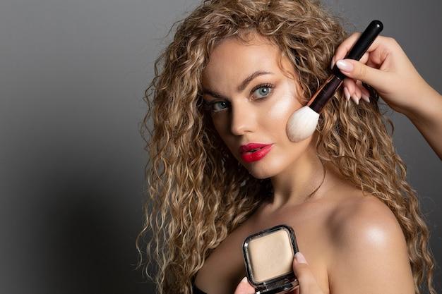 グラマーな女性の顔に固定パウダーを塗るメイクアップアーティスト。コピースペース