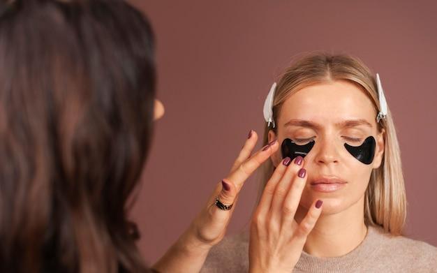 Визажист наносит гидрогелевые повязки на глаза женщине