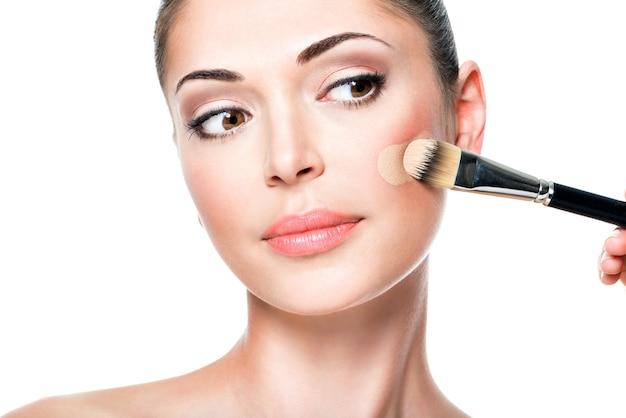여자 얼굴에 리퀴드 톤 파운데이션을 적용하는 메이크업 아티스트