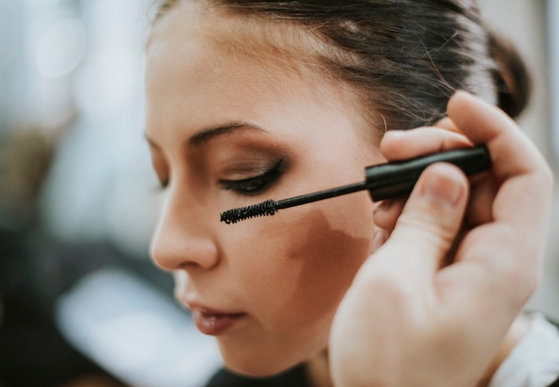 Makeup artist applying mascara onto the model