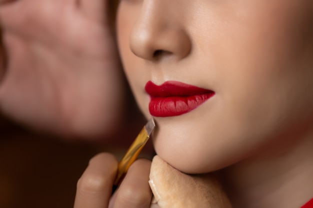 Makeup artist applying red lipstick on beautiful model mouth by using lip brush