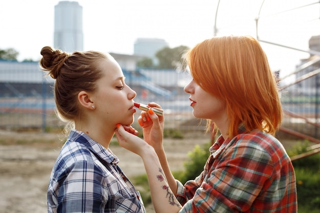 Makeup artist applying red lipstick on lips