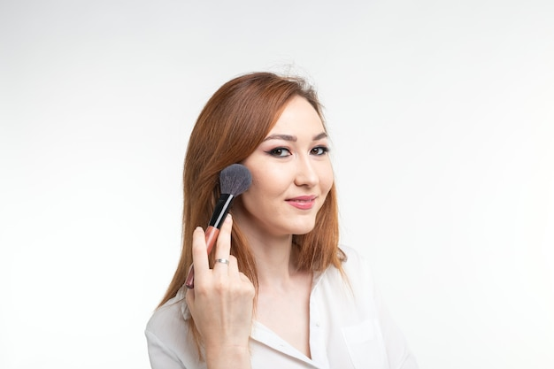 Визажист, концепция красоты и косметики - корейский визажист с кистями для макияжа на белой стене