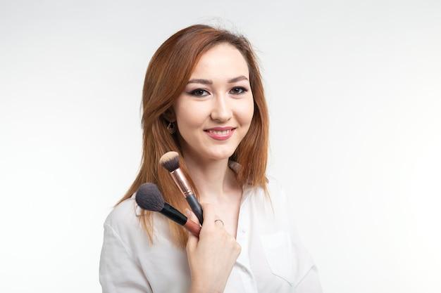 Визажист, концепция красоты и косметики - корейская визажистка с кистями для макияжа