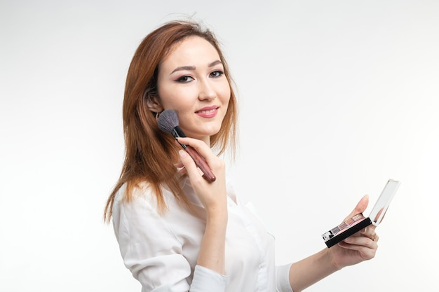 Makeup artist, beauty and people concept - beautiful korean young woman holding palette of colorful eye shadows and brushes on white wall