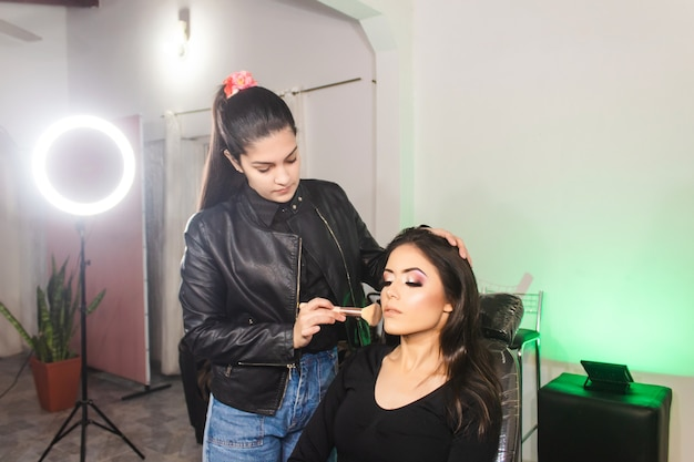 Makeup artist blurring different areas of a beautiful young girl's face in the beauty salon.