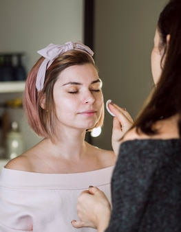 Makeup artist cleaning face of client