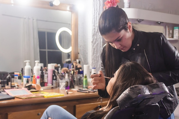 ビューティーサロンで美しい若い女性の唇を描くことに集中しているメイクアップアーティスト。
