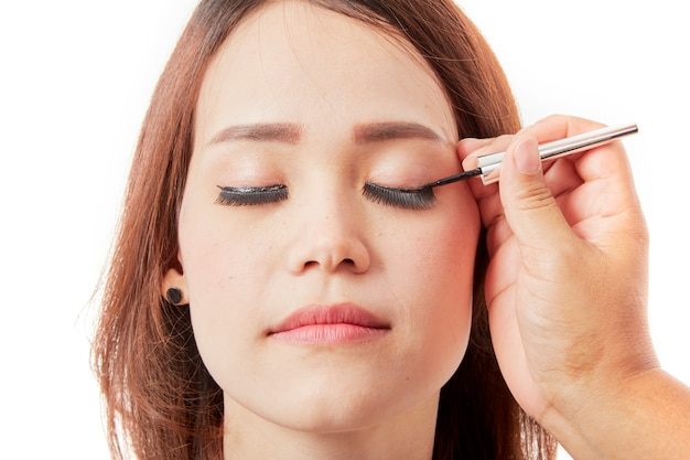 Makeup artist glues eyelashes on client