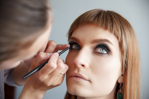 Makeup artist glues false eyelashes