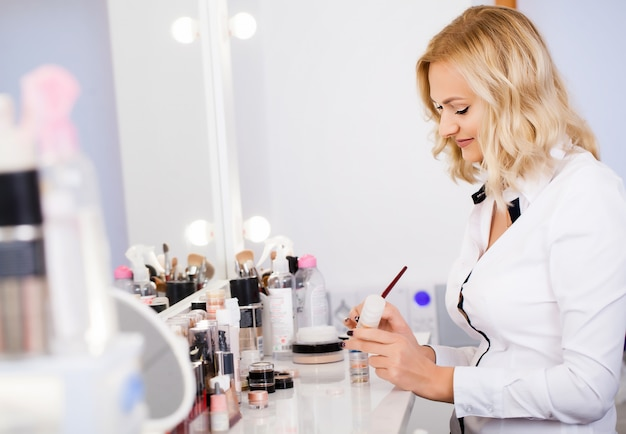 Makeup artist at his workplace in the mirror preparing tools to get started