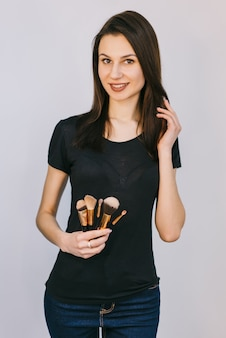 Makeup artist holding brushes. portrait of beautiful woman. beauty makeup professional stylist.