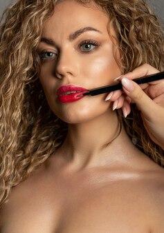 きれいな女性の唇の近くに口紅のブラシを保持しているメイクアップアーティスト。クローズアップスタジオポートレート