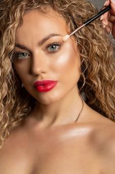 女性の目の近くに化粧ブラシを保持しているメイクアップアーティスト。クローズアップスタジオポートレート
