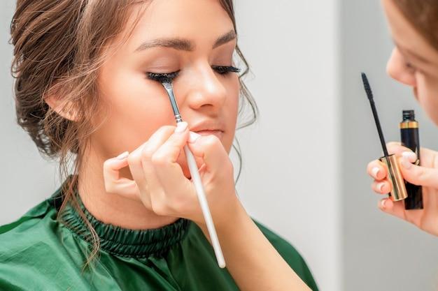 メイクアップアーティストが美しい若い女性の目にまつげパウダーを塗っています、クローズアップ。