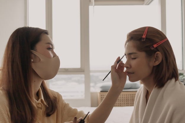 Makeup artist is applying makeup on client eyes
