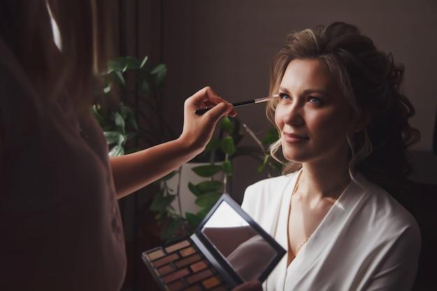 Визажист сделал свадебный макияж для симпатичной молодой женщины-невесты в день свадьбы в гостиничном номере