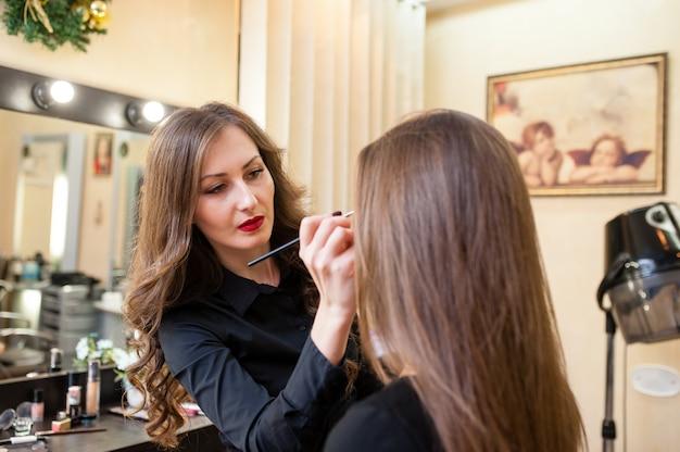 Визажист делает макияж красивой девушки
