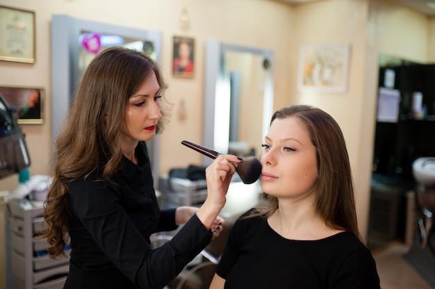 Визажист делает макияж красивой женщины