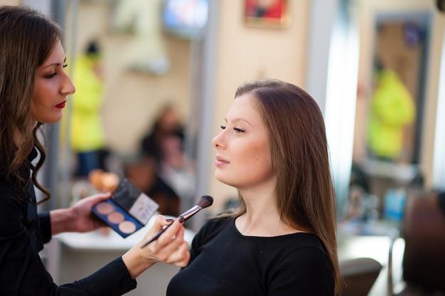 Визажист делает макияж красивой женщине