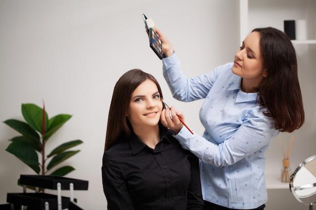 Визажист делает профессиональный макияж клиенту у себя дома