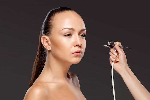 Makeup artist making makeup for model with aerograph