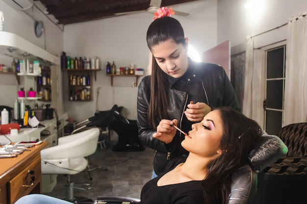 Makeup artist painting the lips of a beautiful young girl in the beauty salon.