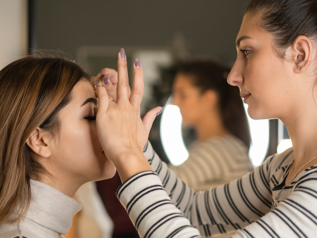 Makeup artist paints eyebrow of a young woman with brush near mirror