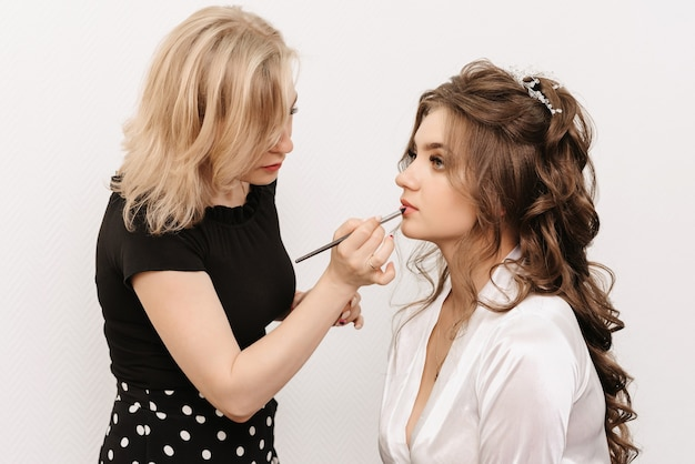 Makeup artist paints the lips of a caucasian bride with a lip brush in a professional beauty salon