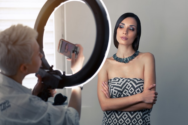 Makeup artist photographs on a mobile phone the result of his work