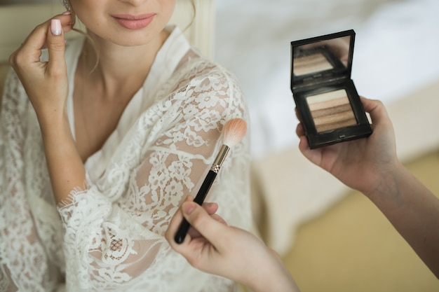 Makeup artist preparing bride before the wedding in a morning