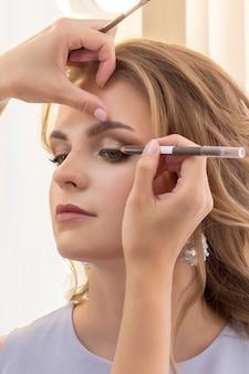 Визажист делает макияж девушке-модели. свадьба, вечерний макияж, натуральный макияж. визажист наносит тени на веки. вертикальное фото