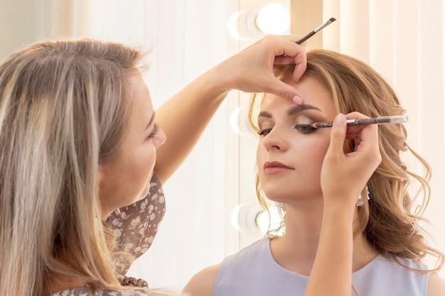 Визажист делает макияж девушке-модели. свадебный макияж, вечерний макияж, натуральный макияж. визажист наносит тени на веки.