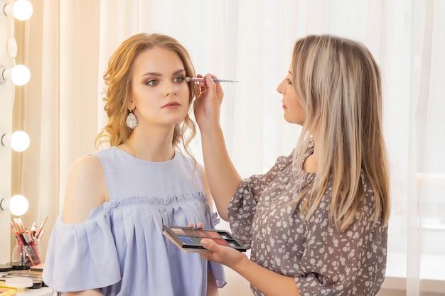 Визажист делает макияж на девушке-модели