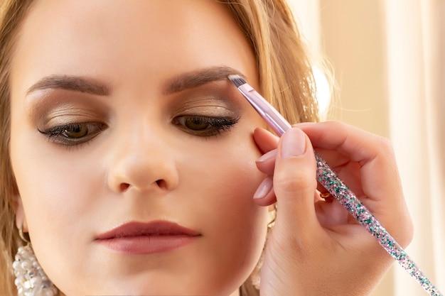 メイクアップアーティストが女の子モデルにメイクをします。眉毛にアイシャドウをブラシで塗ります。美しい少女モデル、肖像画。メイクのヌードカラー。結婚式、イブニングメイク。