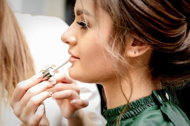ビューティーサロンで美しい若い白人女性の唇にリップグロスを適用するメイクアップアーティストの手