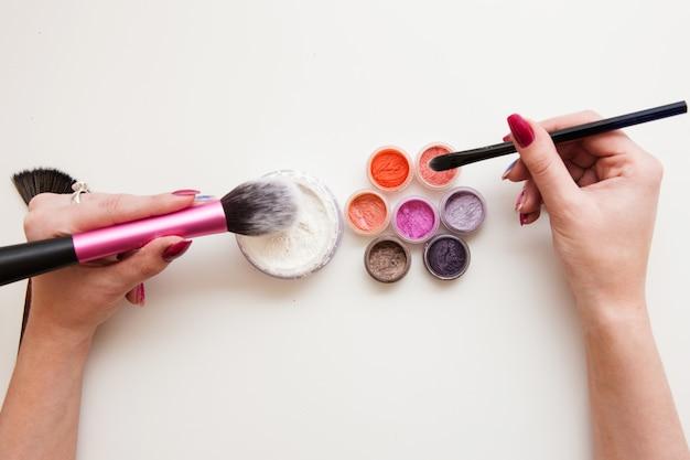 Набор визажиста. кисти, пудра, пигменты и женские руки на белом фоне. профессиональные средства и тени для макияжа глаз.