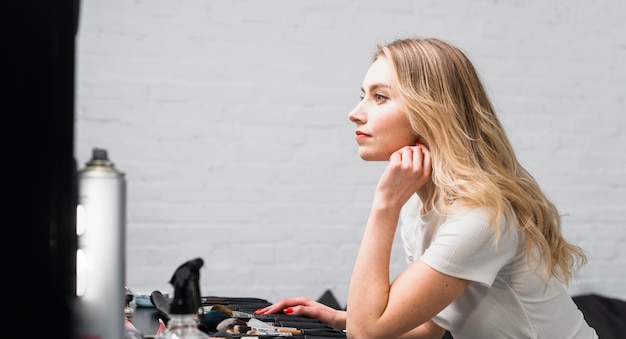 Makeup artist sitting at dressing table