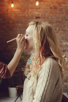 Makeup artist with beautiful blond woman