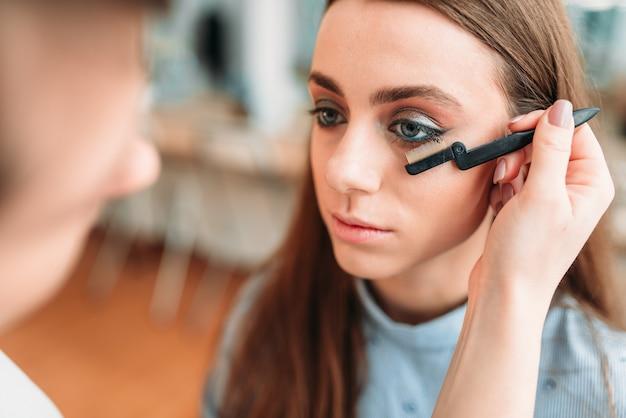手でブラシを持つメイクアップアーティストは、美容スタジオで女性のまつげを扱う